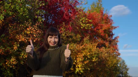 wol : A young woman in a green knitted sweater shows thumbs up against the background of multicolored foliage in a city park in Indian summer.