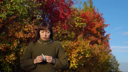 wol : A young sick woman in a green knitted sweater sneezes and blows her nose against the background of multi-colored foliage in the city park in Indian summer.