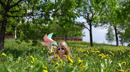 szőke : Little cute girl playing with a multicolored pinwheel, a happy child is sitting in dandelions on a spring sunny day. Stock mozgókép