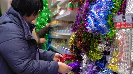 pozlátko : An adult woman chooses Xmas toys and tinsel in the mall, she buys the festive attributes in front of Christmas Eve and the New Year. Dostupné videozáznamy
