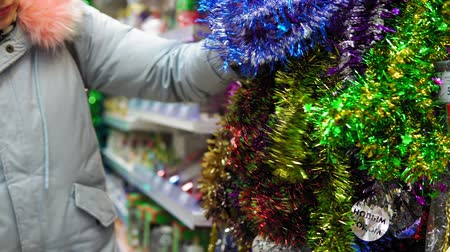pozlátko : Young attractive girl in the store chooses multicolored tinsel decoration for the Christmas tree, Xmas decoration.