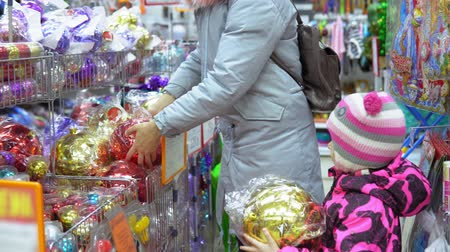 pozlátko : The family chooses multicolored big balls for the Christmas tree, mom and a cute child in the mall buy festive attributes in front of Christmas Eve and New Year.