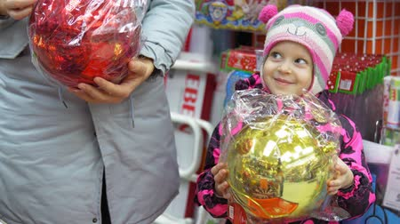 падуб : The family chooses multicolored big balls for the Christmas tree, mom and a cute child in the mall buy festive attributes in front of Christmas Eve and New Year.