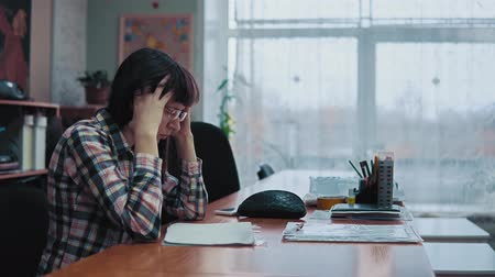 tiredness : A young woman in a checkered shirt is having a headache, she grabs her dark hair and lowers her head above the office desk, sitting against the window. The girl has stress and fatigue.