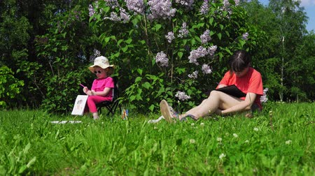 šeřík : A young mother and a pretty blonde little girl paint next to a blooming lilac in the park on a spring sunny day, camera movement left to right Dostupné videozáznamy