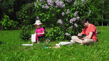 leylak : A young mother and a pretty blonde little girl paint next to a blooming lilac in the park on a spring sunny day, camera movement left to right Stok Video