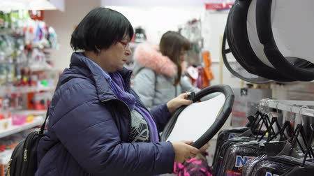 fedél : A mature woman in a blue jacket chooses a soft pad on the steering wheel of a car in the supermarket in the car accessories department.