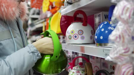 fluitketel : A young woman in a gray coat chooses a green steel whistling kettle in the supermarket in the kitchenware department.