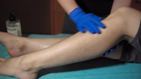 esfregar : The cosmetologist applies a special cream on the female leg of the client before epilation with a thick sugar paste, dolly shot.