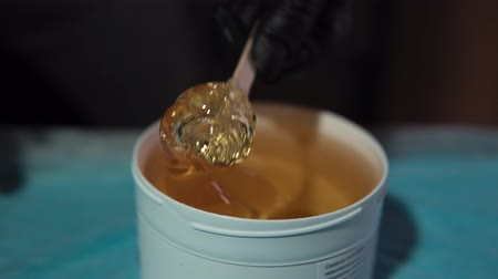 takes : Hands masters in black protective gloves takes a thick yellow caramel paste from a white jar.