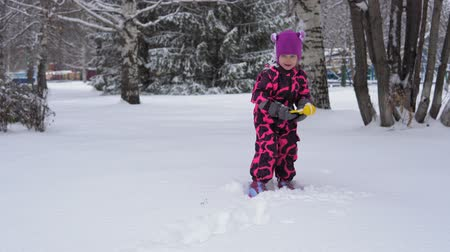 holiday makers : A cute european little girl in a pink winter jumpsuit plays with snow. A happy child makes round white snowballs with a special plastic clamp on a winter day.