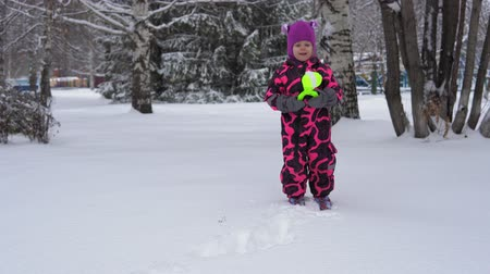 зажим : A cute european little girl in a pink winter jumpsuit plays with snow. A happy child makes round white snowballs with a special plastic clamp on a winter day.
