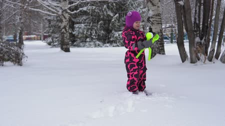зажим : A cute little girl in a pink winter jumpsuit plays with snow. A happy child makes round white snowballs with a special plastic clamp on a winter day.
