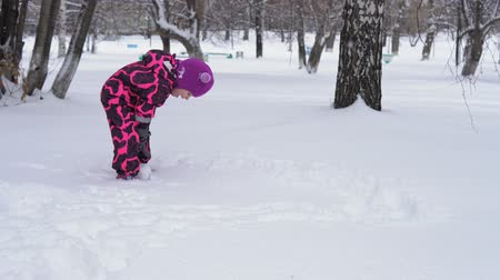 macacão : Cute little girl in pink jumpsuit makes a snowman. The child rolls a snowball through the snow, the white ball increases in size, fun games in winter.