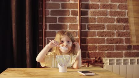 yoghurt : A cute little girl eats yogurt from a big white jar near a brick wall for Breakfast. The child is dressed in yellow pajamas. Stock Footage