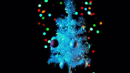 bombki : White artificial Christmas tree with colored balls rotates next to multi-colored light bulbs on a black background, seamless looping. Wideo