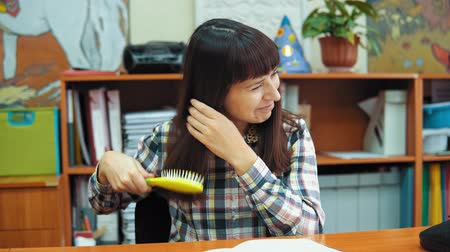 rastrelliera : A young female teacher dressed in a checkered shirt sits at a table in the classroom, she is combing her dark hair the background of a rack with books and documents. Filmati Stock