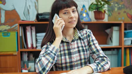písanka : A young female teacher dressed in a checkered shirt sits at a table in the classroom, happy girl talking on the phone on the background of a rack with books and documents.