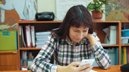 caderno : A young female teacher dressed in a plaid shirt sits at a table in the classroom, she is looking for information using a browser on a smartphone.
