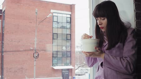 pauzinhos : A young woman in a purple jacket eating noodles from a paper bowl, she sits on the windowsill against a brick building, dolly shot.