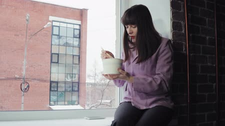 kluski : A young woman in a purple jacket pours seasoning from a bag into a paper bowl of food, she sits on the windowsill against a brick building, dolly shot.