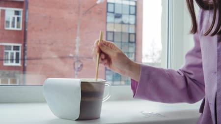 ramen : A young woman in a pink jacket prepares instant noodles, she stands by the window against an office brick building. The girl mixes the food with chopsticks in a paper bowl,dolly shot. Stock Footage