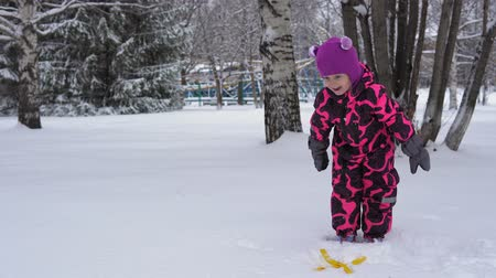 macacão : Cute little girl in pink jumpsuit throws a round snowball, fun games with snow in winter.
