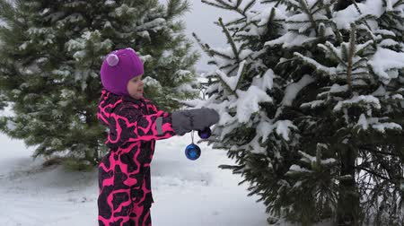 macacão : A little cute European girl in a pink winter jumpsuit decorates a fluffy snow-covered Christmas tree with a colored ball. The child is preparing for Christmas or the new year.