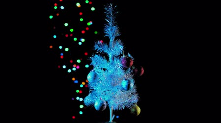 çelenk : White artificial Christmas tree with colored balls rotates against the background of a flashing electric garland with colored lights in the dark, seamless looping.