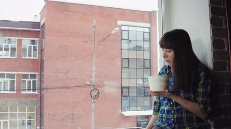 kluski : A young woman in a blue plaid shirt is eating instant noodles from a paper bowl, she is sitting on the windowsill against the background of a brick office building, dolly shot. Wideo