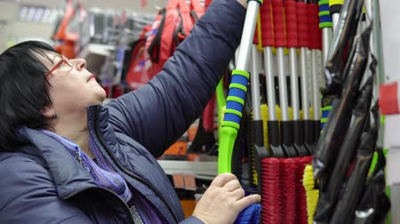 süpürge : A mature woman in a blue jacket chooses a brush with scraper in the supermarket in the car accessories department.