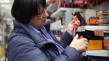besom : A mature woman in a blue jacket chooses a brush with scraper in the supermarket in the car accessories department.