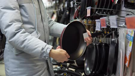 scaffale supermercato : A young woman in a gray coat chooses a non-stick frying pan in the supermarket in the kitchenware department.