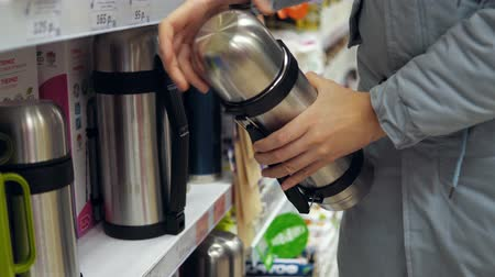 scaffale supermercato : A young woman in a gray coat chooses a steel thermos in the supermarket in the kitchenware department.She cares about her health and nature. Filmati Stock