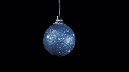 bombki : Close-up shot of glistening azure ball rotates clockwise on black background, Christmas and New Year decoration isolated on dark, seamless looping.
