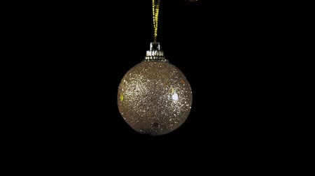 bombki : Golden ball rotates clockwise on black background, Christmas and New Year decoration isolated on dark, seamless looping.