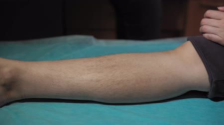 dermatologia : Whose foot with long black hairs on a blue disposable bed sheet,dolly shot.