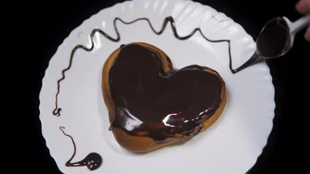 houska : Someone decorates dark topping white plate with a bun in the shape of a heart covered with chocolate. Dostupné videozáznamy