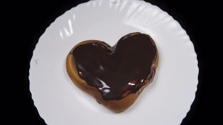 houska : Top view of a heart shaped bun chocolate covered, baking lies on a white plate and rotates on a black background, seamless looping. Dostupné videozáznamy
