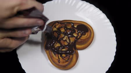 houska : Someone pours chocolate on a sweet heart-shaped bun, fresh baking lies on a white plate and rotates counterclockwise on a black background, top view.