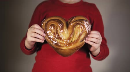 bestrew : An unidentified child in a red t-shirt with long sleeves holds a sweet bun in the form of a heart.