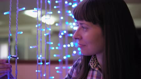 lampadine : Portrait of a young woman in a plaid shirt considering the threads of a blue electric garland, side view.