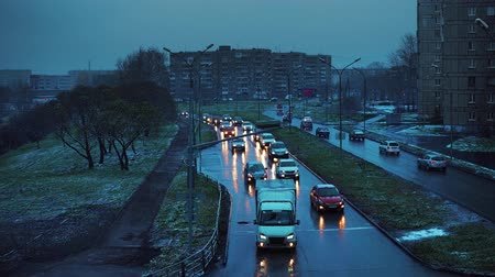 meteorologia : Bad weather, sticky white snow on trees and green grass. The cars drive carefully on a wet road with lighted headlights at dusk in autumn. Stock Footage