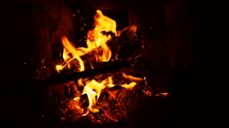 gasolina : A iron poker stir and prod dry firewood in fireplace, warm cozy burning fire in a brick furnace, slow motion. Vídeos