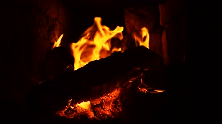hořlavý : Close-up shot of hot fireplace full of dry firewood, warm cozy burning fire in a brick furnace, slow motion.