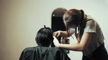 grzebień : Mature woman having her hair cut at the hairdressers. Hairdresser trimming female dark hair with scissors in beauty salon.