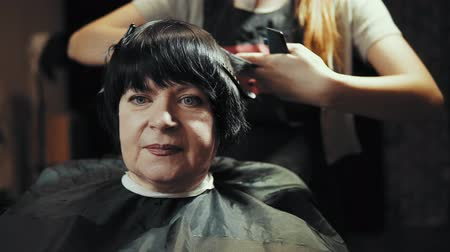 taberna : Mature woman having her hair cut at the hairdressers. Hairdresser trimming female dark hair with scissors in beauty salon.