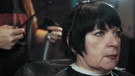 grzebień : Mature woman having her hair cut at the hairdressers. Closeup view of a hairdressers hands cutting hair with scissors.
