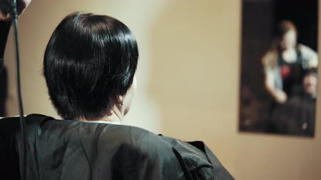 kısa : Mature woman having her hair cut at the hairdressers. Girl hairdresser blows hairdryer trimmed hair from the female client, close-up view from the back. Stok Video