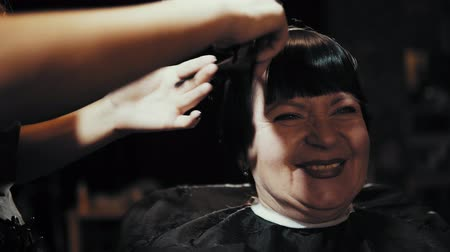 taberna : Mature woman having her hair cut at the hairdressers. Closeup view of a hairdressers hands cutting female dark hair with a thinning shears in beauty salon.